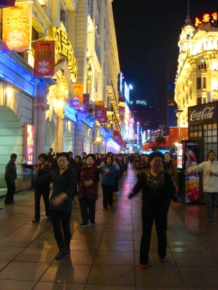 One of Shanghai's main thoroughfares is full of neon... and group activities like dancing